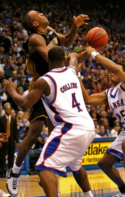 Missouri forward Leo Lyons tries to hold onto the ball as Kansas guards Sherron Collins and Brandon Rush grab at Lyons' forearm during the game's second half on Jan. 15, 2007, at Allen Fieldhouse. The Tigers attempted a failed three-point play in the game's final 11 seconds and lost 80-77 to the Jayhawks.